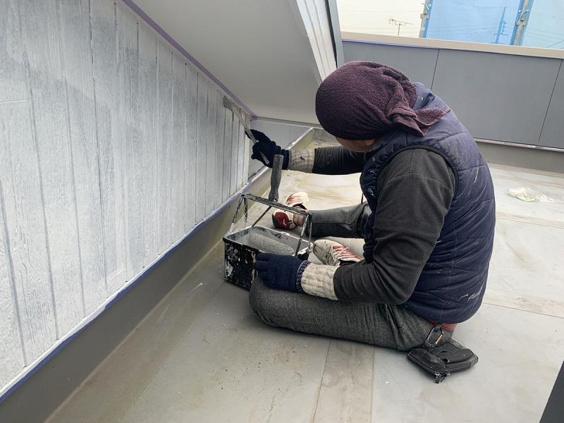 木目調の外壁を刷毛で下塗り中
