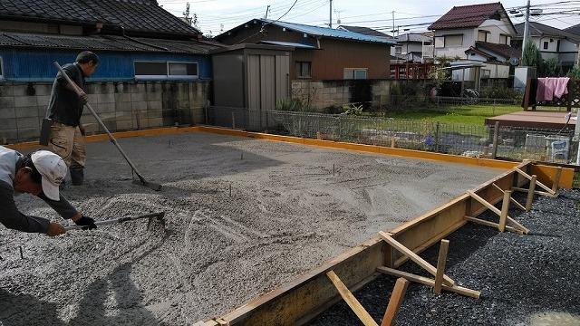 流し込んだコンクリートを板トンボで全体的に広げている