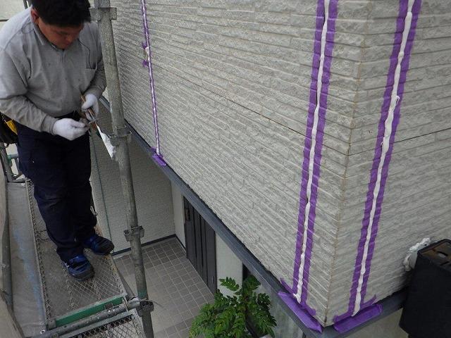 外壁塗装前のベランダのシーリング材とマスキングテープと職人