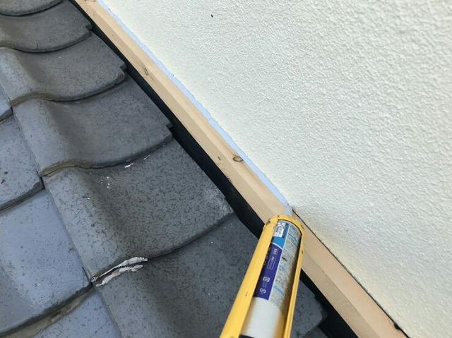 降り壁に雨押え板金のためのコーキング剤塗布中