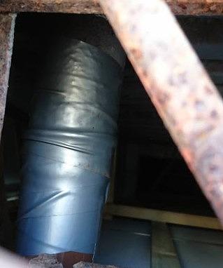 ひび割れた排水管に防水テープを巻く