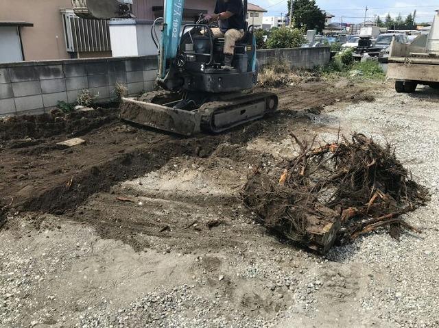 掘り出した切り株の穴を重機で地面をならしているところ