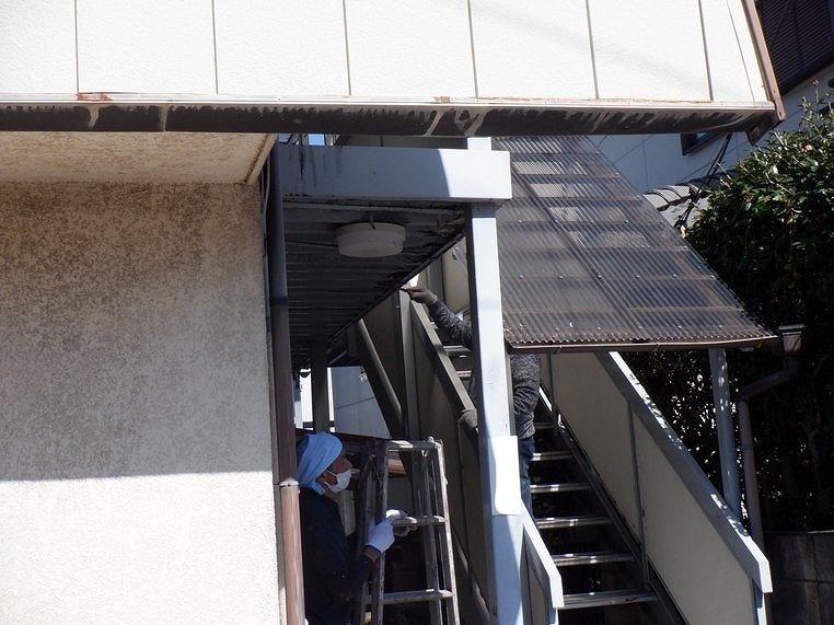 脚立とスクレーパーでアパートの鉄骨をケレン作業