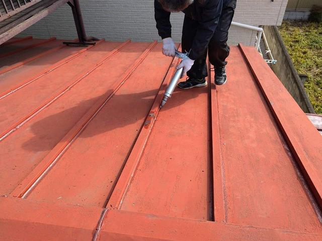 瓦棒と板金屋根のすき間にコーキング充填中