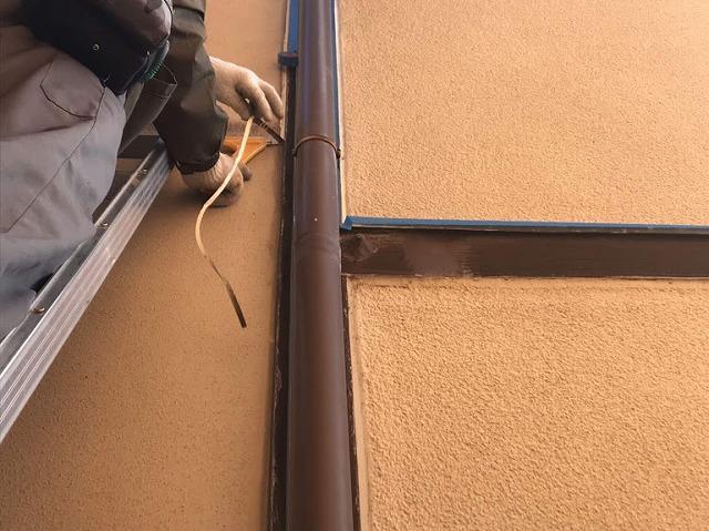 雨樋後ろの柱左側のコーキングを垂直に剥がしているところ