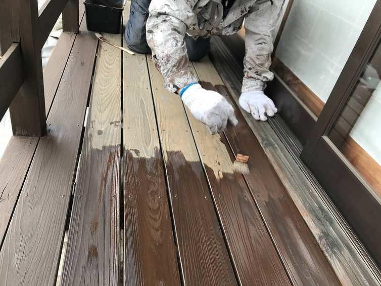 床板の上で木材保護塗料の塗装作業