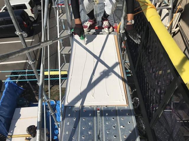 ケイカル板の裏側に接着剤を塗っているところ