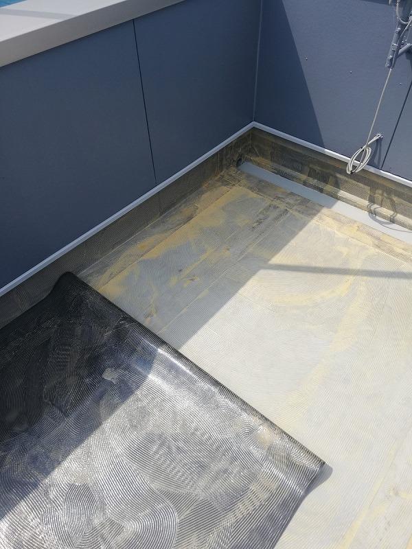 既存の防水シートの上に新しい防水シートを張り合わせる
