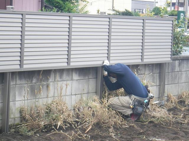 目隠しフェンスを支柱の下から取り付け作業中