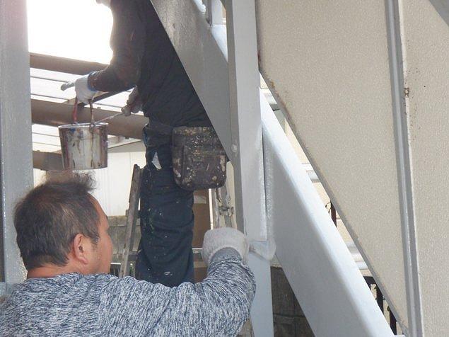 アパートの階段の側板のすき間に刷毛で上塗り