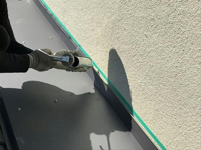 マスキングテープをして雨押え板金にコーキング剤塗布中