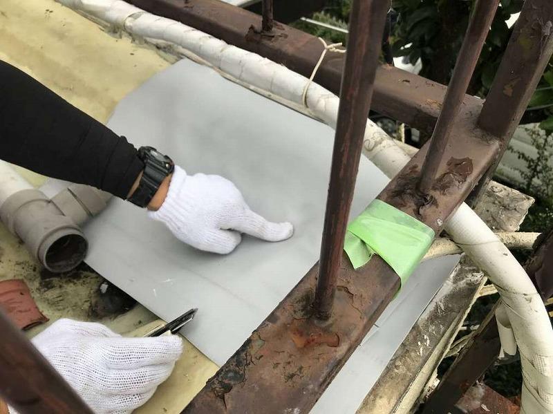 バルコニーの隅に合わせて防水シートを切るところ