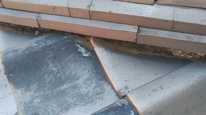 隅棟の漆喰の下から土がしみ出ている