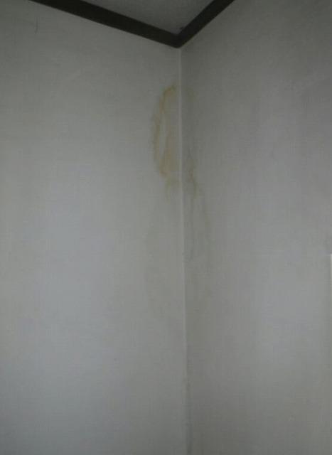 穴の開いた軒天井の裏のトイレの茶色いシミ