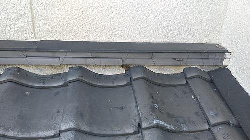 雨押え板金の下の漆喰が一部取れて土が見えている