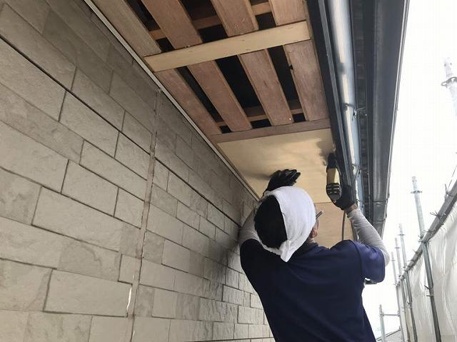 足場から見て軒天井の下地ラワン耐水合板をタッカーで打ち付けているところ