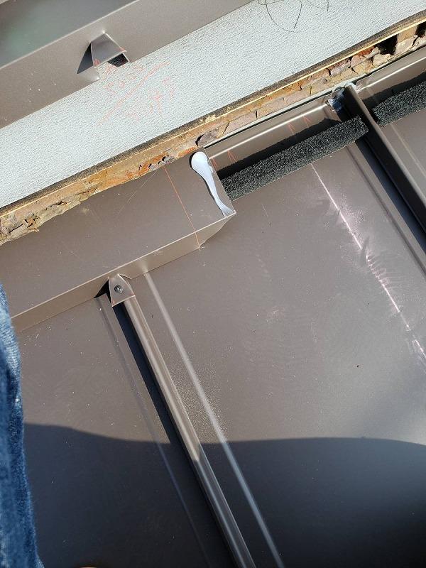 面戸の黒い防水テープの上に雨押え板金