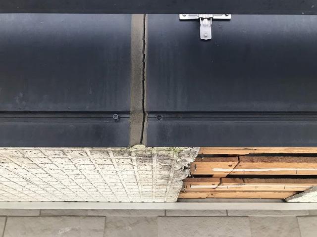 足場から見た鼻隠し板金のコーキングの切れた状態と軒天井と下地木材