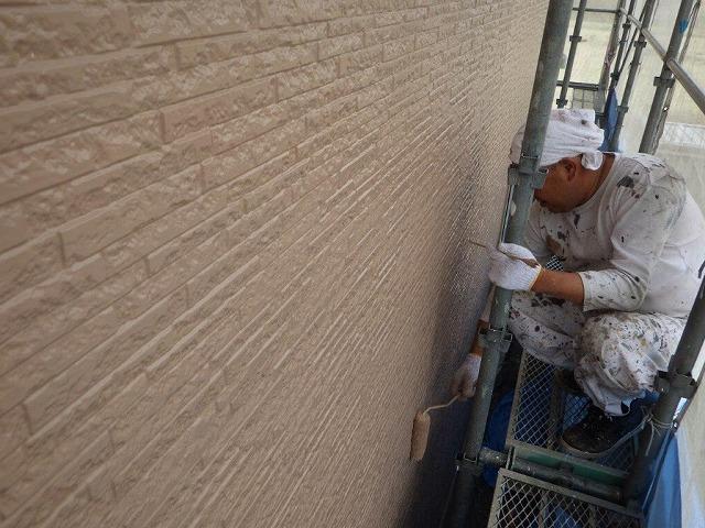 ローラーと刷毛をもって踏み板の上で塗装作業中