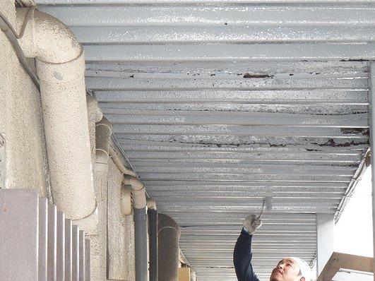 アパートの通路の鉄骨の天井にローラーで上塗り