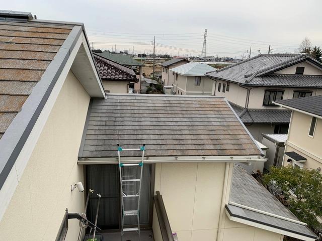 ベランダに脚立をかけて雨漏りしているスレートの屋根を調査