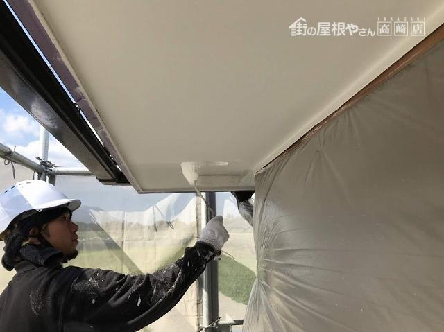 足場から見た軒天井を塗装屋さんがローラーで塗っているところ