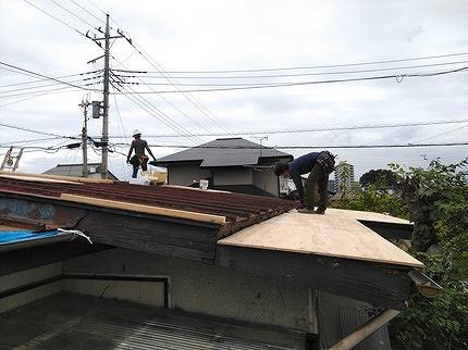 南東の一段低い屋根に野地板を職人さんが張っているところ