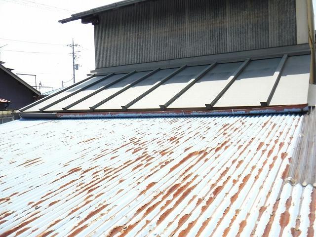 錆びたトタンの波板とその奥の変形した雨樋