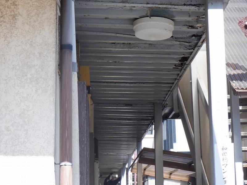 アパートの通路奥で鉄骨の天井ヤスリ掛け