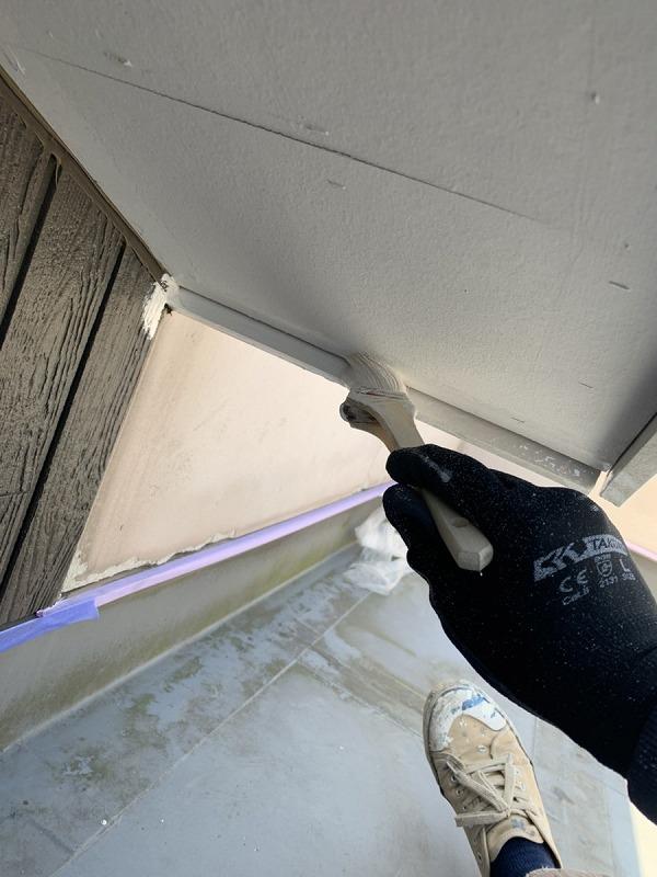 軒天井の隅を刷毛にて塗装中