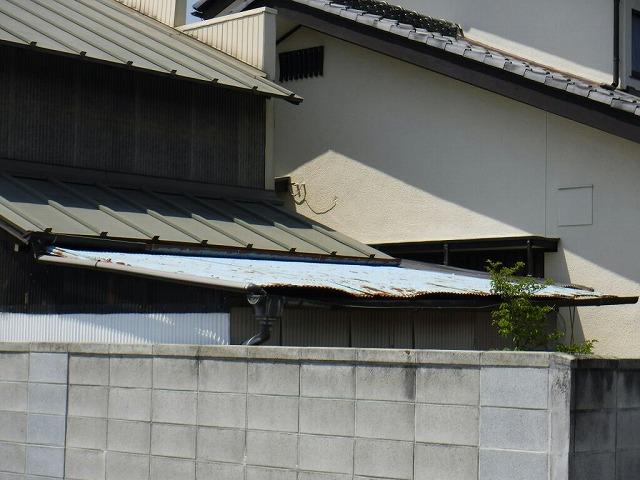 錆びたトタンの波板と変形した雨樋