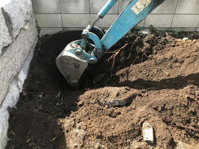 木の切り株を重機で掘っているところ