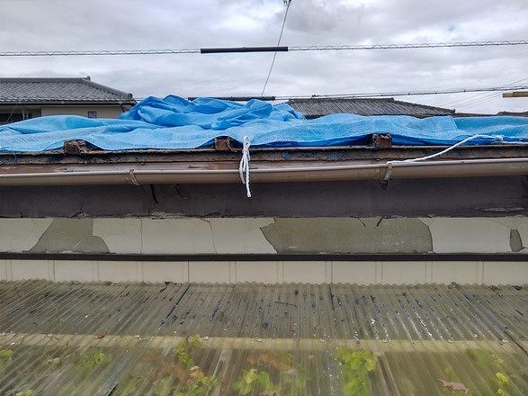 トタン屋根の上のブルーシートと欠けている漆喰壁