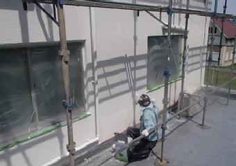 外壁に仕上げの上塗りをする作業員